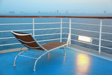 Illuminated solitary highlighted deck-chair on ship overlooking