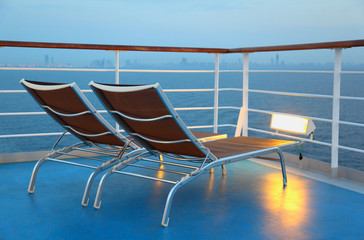 Two deck-chair are on the ship overlooking the city in evening