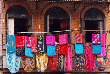 Storefront of old nepal textile shop with many multicolored garm
