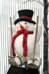 snowman with black hat on skis