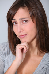 Young woman looking at camera with hand on chin