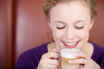 lächelnde frau trinkt latte macchiato