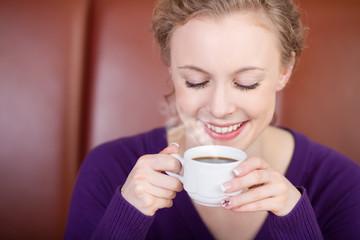 lächelnde frau trinkt dampfenden kaffee
