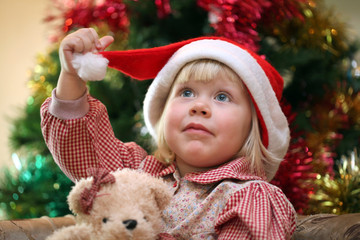 Small girl with toy near and christmas tree on the background