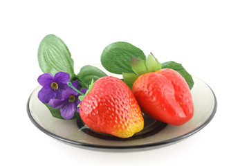 Artificial flowers and strawberries on saucer.