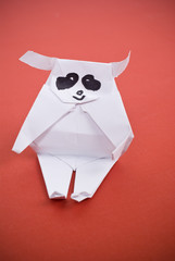 Panda out of paper on a red background