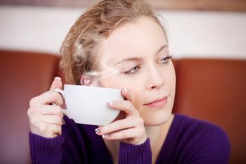 schöne frau mit dampfendem kaffee