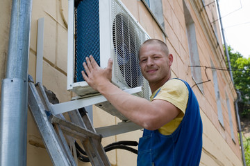 Young setup man installs the new air conditioner.