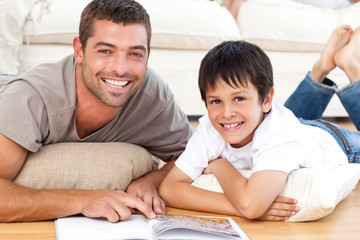 Portrait of a father and son reading a book on the floor