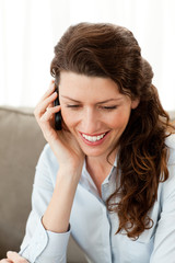 Smiling businesswoman on the phone while resting on the sofa