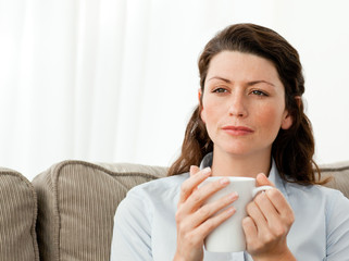 Thoughtful woman drinking coffee on the sofa