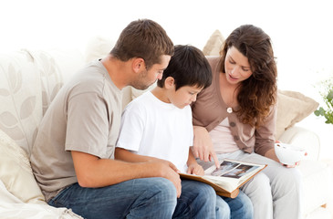 Happy family looking at a photo album together on the sofa