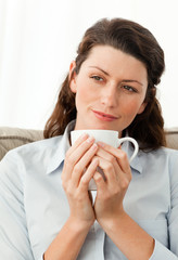 Pretty woman holding a cup of coffee sitting on the sofa