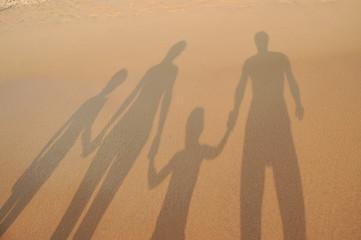 Family shadows on beach sand