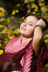 Young beautiful smiling woman turned to the sun with closed eyes
