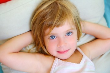 blond relaxed girl on pillow blue eyes smiling