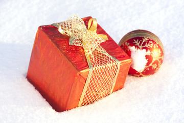 Christmas gifts and decorative ball in the snow