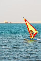 windsurfer, blue sea and yellow sail on sunset