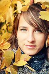 Beautiful girl among autumn leaves