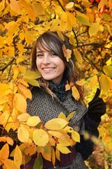 Beautiful girl among yellow autumn leaves