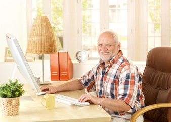 Happy senior man using computer