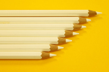 White pencils on yellow paper.