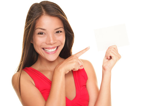 Beautiful smiling woman pointing at blank gift card sign