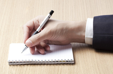 main et stylo écrivant sur bloc notes calepin