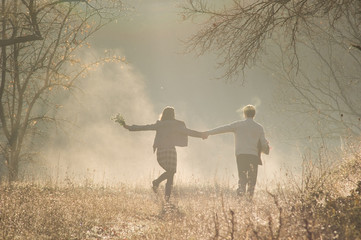 Young couple in the autumn park in the cool fog morning