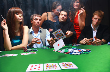 Stylish man in black suit folds two cards in casino poker