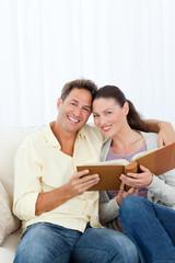 Portrait of a happy couple looking a photo album