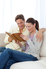 Happy couple looking at pictures on a photo album while relaxing