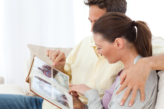 Lovely couple looking at pictures on a photo album on the sofa