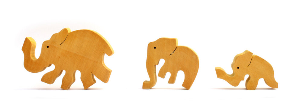 Three wooden toy elephants marching in a row