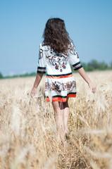 Beautiful woman walk in wheat field on sunny summer day.