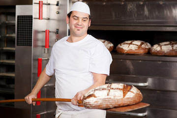 zufriedener bäcker holt brot aus dem ofen