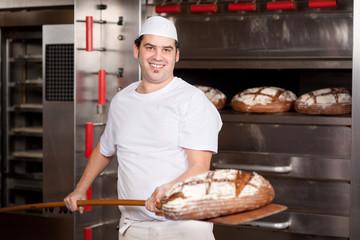 bäcker mit brotschieber vor dem ofen