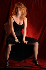 Lachende rothaarige Frau mit vollen Locken im schwarzen Kleid
