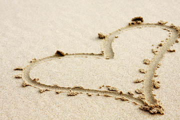 hearts drawn in the sand with seafoam and wave