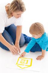 Mother and son drawing a small house together