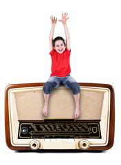 bambino seduto sopra radio vintage