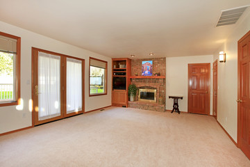 Empty living room with fireplace and doors