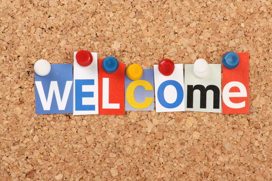 The word Welcome in magazine letters on a notice board