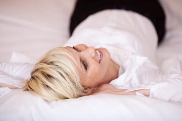 blonde frau entspannt auf dem bett