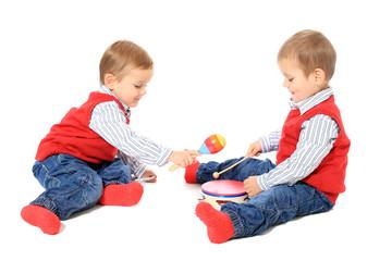 Zwillinge spielen mit Musikinstrumenten / freigestellt