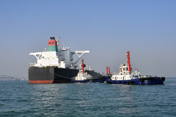 Oil tanker and tugboats