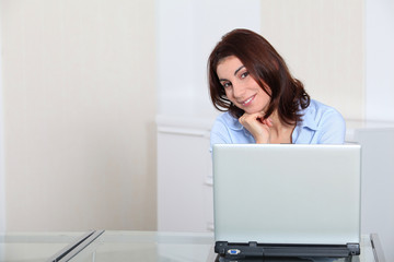 Portrait of businesswoman in front of laptop computer