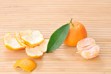 fresh orange with green leaf and a peeled on a bamboo plate