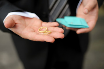 groom holding two gold wedding rings in palm