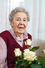 Portrait of senior smiling woman with bunch of roses